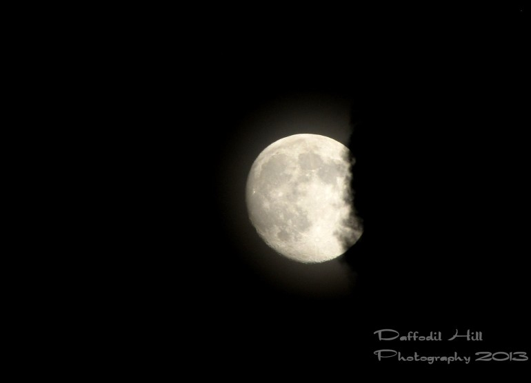 A hand held shot of the moon being eating by a cloud.